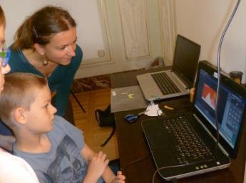 """Joanna Koźuch, vedúca tvorivej dielne, s deťmi pri nakrúcaní animovaného filmu """"Cesta okolo sveta za štyri dni"""""""